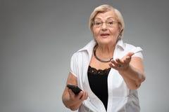 Mulher idosa que guarda o smartphone Foto de Stock