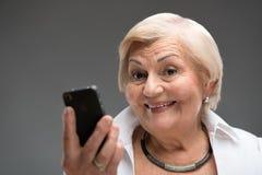 Mulher idosa que guarda o smartphone Imagens de Stock