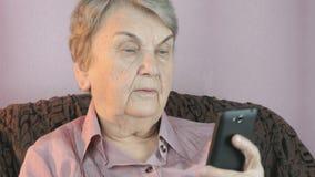 Mulher idosa que guarda o smartphone dentro vídeos de arquivo