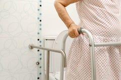 Mulher idosa que guarda sobre o caminhante no toalete imagem de stock royalty free