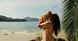 Mulher idosa que joga com o bebê na praia filme