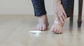 Mulher idosa que põe o creme sobre os pés inchados imagens de stock royalty free