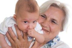 Mulher idosa que prende um recém-nascido fotografia de stock