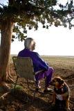Mulher idosa que presta atenção a Sunset-5956.jpg imagens de stock royalty free
