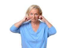 Mulher idosa que puxa na pele em suas queixadas imagem de stock