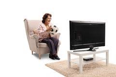 Mulher idosa que senta-se em uma poltrona com bola de futebol e watchi imagem de stock royalty free