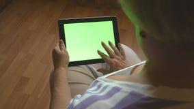 Mulher idosa que senta-se no sofá em casa e que usa um PC digital da tabuleta com tela verde, vista traseira PC da tabuleta em um video estoque