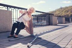 Mulher idosa que tenta levantar-se após a queda para baixo imagem de stock royalty free