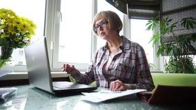 A mulher idosa que usa Internet banking na casa vídeos de arquivo