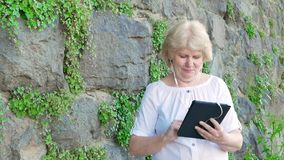 Mulher idosa que usa o tablet pc com fones de ouvido Parede do vintage da pedra selvagem no fundo filme