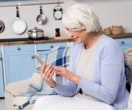 Mulher idosa que usa o telefone celular em casa imagens de stock royalty free