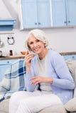 Mulher idosa que usa o telefone celular em casa foto de stock royalty free
