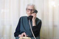Mulher idosa que usa o telefone dentro Fotografia de Stock
