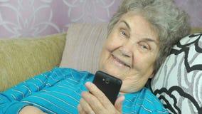 Mulher idosa que usa um smartphone filme