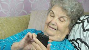 Mulher idosa que usa um telefone celular filme
