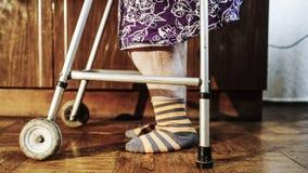 Mulher idosa que vai lentamente com a ajuda do caminhante Imagem de Stock Royalty Free