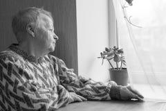 A mulher idosa senta e olha para fora a janela Imagens de Stock Royalty Free