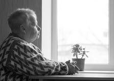 A mulher idosa senta e olha para fora a janela Fotografia de Stock Royalty Free