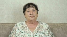 A mulher idosa sorri, bebe a água, mostra o polegar acima video estoque