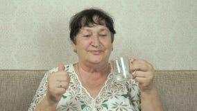 A mulher idosa sorri, bebe a água, mostra o polegar acima vídeos de arquivo