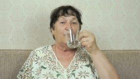 A mulher idosa sorri e bebe a água de um vidro filme