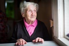 A mulher idosa surpreendida olha fixamente fora da janela feliz foto de stock