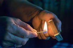 A mulher ilumina um fósforo, fogo de um fósforo Fotos de Stock