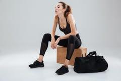 Mulher impressionante cansado do esporte que relaxa na caixa no estúdio Imagens de Stock