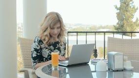 Mulher impressionante que senta-se em um café com um vidro do suco de laranja e que datilografa uma mensagem em um portátil video estoque