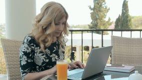 Mulher impressionante que senta-se em um café com um vidro do suco de laranja e que datilografa uma mensagem em um portátil vídeos de arquivo
