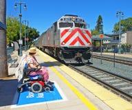 A mulher incapacitada que presta atenção a seu trem chega Fotografia de Stock Royalty Free