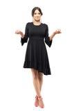 Mulher incerta encantador de sorriso no vestido preto que shrugging ombros com braços aumentados Fotografia de Stock Royalty Free