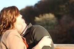 A mulher inclina a cara ao céu enquanto o homem farpado beija seu pescoço Imagens de Stock Royalty Free