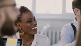 A mulher incorporada de sorriso positiva nova na reunião da equipe, assistente do gerente do afro-americano profissional traz o  vídeos de arquivo