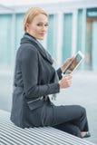 Mulher incorporada que guarda a tabuleta fora do escritório Imagens de Stock