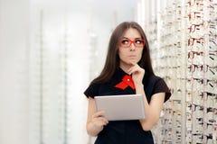 Mulher indeciso com a tabuleta do PC na loja ótica Imagens de Stock