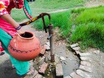 Mulher indiana com potenciômetro da água fotografia de stock