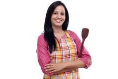 Mulher indiana nova que mantém o utensílio da cozinha contra o branco imagem de stock