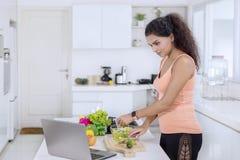 Mulher indiana que olha receitas em um portátil imagem de stock royalty free