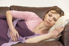 Mulher indisposta e que encontra-se no sofá Fotos de Stock