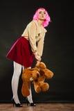 Mulher infantil com o brinquedo do cão no preto imagem de stock