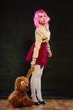 Mulher infantil com o brinquedo do cão no preto foto de stock royalty free