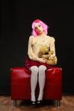 Mulher infantil e urso de peluche que senta-se no sofá fotografia de stock
