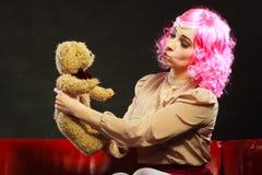 Mulher infantil e urso de peluche que senta-se no sofá imagens de stock