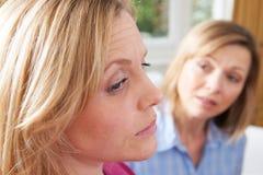Mulher infeliz na conversação com amigo ou conselheiro imagem de stock
