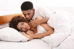 Mulher infeliz que encontra-se na cama, seu noivo que desculpa-se imagem de stock royalty free