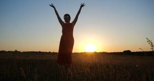 Mulher inspirada em uma dança vermelha do vestido em um campo horizonless no por do sol video estoque