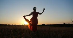 Mulher inspirada em uma dança vermelha do vestido em um campo horizonless no por do sol fotografia de stock
