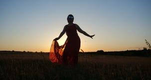 Mulher inspirada em uma dança vermelha do vestido em um campo horizonless no por do sol fotografia de stock royalty free