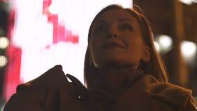 Mulher inspirada que está o fundo iluminado do quadro de avisos, apreciando a noite da cidade video estoque